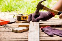Bakgrundshantverkarehjälpmedlet liksom den gamla hammaren med måttband och litet spikar och såg med utomhus- sikt för handske och Royaltyfria Bilder