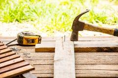 Bakgrundshantverkarehjälpmedlet med den gamla hammaren med måttband och litet spikar på träbakgrund och utomhus- sikt Royaltyfria Bilder
