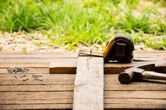 Bakgrundshantverkarehjälpmedlet med den gamla hammaren och litet spikar och måttbandet på träbakgrund och utomhus- siktslandsstil Royaltyfria Bilder