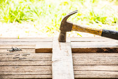Bakgrundshantverkarehjälpmedlet med den gamla hammaren och litet spikar på träbakgrund och utomhus- siktslandsstil Royaltyfri Foto
