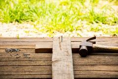 Bakgrundshantverkarehjälpmedlet och den gamla hammaren och litet spikar på träbakgrund och utomhus- siktslandsstil Arkivbilder
