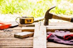 Bakgrundshantverkarehjälpmedlet och den gamla hammaren och litet spikar på träbakgrund och utomhus- siktslandsstil Royaltyfri Fotografi