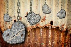 Bakgrundshjärtor av stål med skrapor som hänger på kedjor Royaltyfri Bild