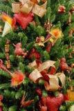 bakgrundsjulen dekorerade den röda treen Arkivbilder
