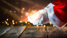 bakgrundsjulen inramninde ferieplats Glödande stjärnor för Santa Claus visning och magiskt damm i öppna händer arkivbilder
