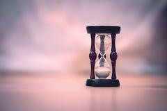 bakgrundsklockan som omfamnar den gråa timglasmannen, målade gravida sandmagekvinnor Royaltyfri Fotografi
