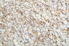 Bakgrundslager av rå oatflakes Arkivfoto