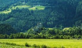 Bakgrundslandskapsikt av den aAncient slotten bland fälten i Tyrol Arkivbild
