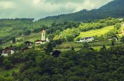 Bakgrundslandskapsikt av en liten alpin by i Tyrol Arkivfoto