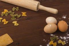 Bakgrundsmatlagning Ägg mjöl, kavel, tolkushka på en trätabell Arkivbild