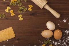 Bakgrundsmatlagning Ägg mjöl, kavel, tolkushka på en trätabell Royaltyfria Foton
