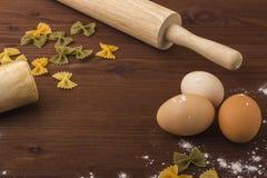 Bakgrundsmatlagning Ägg mjöl, kavel, tolkushka på en trätabell Royaltyfri Foto