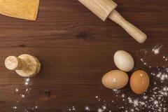 Bakgrundsmatlagning Ägg mjöl, kavel, tolkushka på en trätabell Arkivfoto