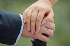 bakgrundsparet hands henne holdingen som att gifta sig av cirkeln som där visar vattenbröllopfrun Royaltyfri Fotografi