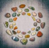 Bakgrundsramcirkel av färgrika havs- och flodstenar Royaltyfri Foto
