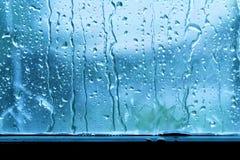Bakgrundsregndroppe på blått för fönsterexponeringsglas royaltyfri bild