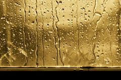 Bakgrundsregndroppe på guld eller guling för fönsterexponeringsglas arkivfoto