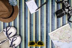 Bakgrundssammansättning från över för sommarferier med tappningkameran, solglasögon, vita skor, sugrörhatten, översikten och note arkivfoto