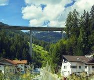 Bakgrundssikt av den alpina byn och den snabba vägen i bergen Arkivbild
