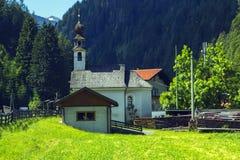 Bakgrundssikt av en liten kyrka i en by i Tyrol Royaltyfri Bild