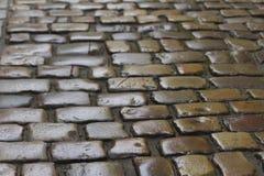 Bakgrundstextur av den gamla coblestonevägen Royaltyfria Bilder