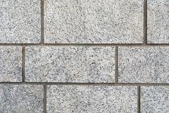 Bakgrundstextur av en grå granittegelstenvägg arkivbild