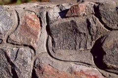 Bakgrundstextur av en vertikal vägg av den naturliga stenen Grov grov yttersida av stenen royaltyfri foto