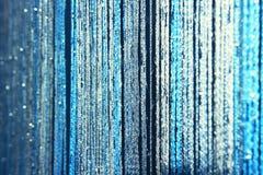 Bakgrundstexturgardiner som göras av blått, dragar med blänker och gör suddig på kanterna Arkivfoto