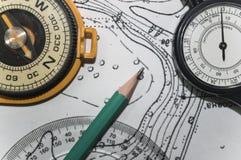 Bakgrundstopografi en blyertspenna en gammal kompass och översikt Arkivfoton