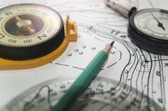Bakgrundstopografiblyertspenna en gammal kompass och översikt Royaltyfri Bild