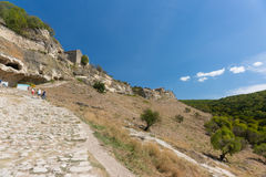 BAKHCHISARAY, REPUBLIC of CRIMEA, RUSSIA - SEPTEMBER 13.2016: Tourists climb to the entrance in the medieval fortress town Chufut-. Kale. A warm Sunny day royalty free stock photography