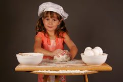 Baking. A cute young girl kneading her dough to make cookies, wearing a chefs hat and apron royalty free stock images
