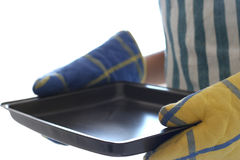 Baking. A lady wearing oven mitts and an apron carrying an empty baking tray stock photography