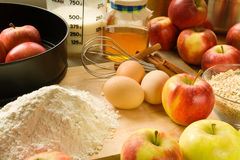 Baking apple pie. Ingredients for baking an apple pie, arranged on a table, including apples, flour, milk, eggs, oat flakes and honey Stock Photo