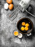 Baking background. Blend eggs with a mixer to make a dough. On a rustic background royalty free stock photography