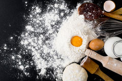Baking background with cake ingredients. On black chalkboard from above bowl flour eggs Royalty Free Stock Photos