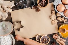 Baking background for Christmas cookies. Recipe paper in the center. Wooden background. Top view Stock Photos