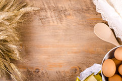 Baking background with ears of wheat, flour, eggs and butter. Free space for text Stock Photography