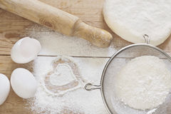 Baking background. Flour, dough, eggs and rolling-pin on wooden table Royalty Free Stock Photo