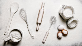 Baking background. Flour, eggs, and different tools - Beaters, spatula, rolling pin and a sieve. Royalty Free Stock Images