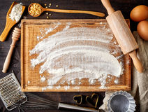 Baking background with flour, eggs and tools. Baking background with cutting board, eggs, sugar, flour, rolling pin, grater and spoons, top view Royalty Free Stock Images