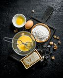 Baking background. Flour with honey and eggs on the cutting Board. On black rustic background stock photography
