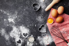 Baking background with flour, rolling pin, eggs, and heart shape on dark kitchen table top view for Valentines day cooking. Flat l