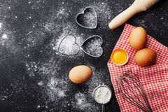 Baking background with flour, rolling pin, eggs, and heart shape on kitchen black table top view for Valentines day cooking.