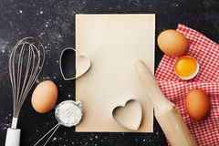 Baking background with flour, rolling pin, eggs, paper sheet and heart shape on kitchen table top view for Valentines day.Flat lay