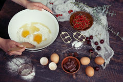 Baking background with ingredients for fruit and chocolate cake. In rustic kitchen.Eggs, flour, chocolate, milk, berries Royalty Free Stock Photos