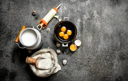 Baking background. Milk, flour, eggs and confectionery syringe for cake. royalty free stock images