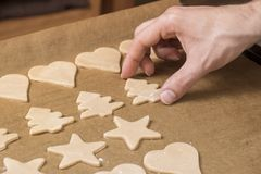 Baking biscuits in advent and christmas at home. Man, hand, fingers, star royalty free stock photo