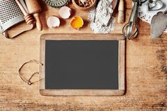 Baking border with vintage cookware, egg and flour. Baking border with an assortment of vintage cookware, egg and flour above a blank school slate with copy stock photo
