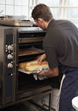 Baking bread. Cook baking bread in a restaurant kitchen stock photos